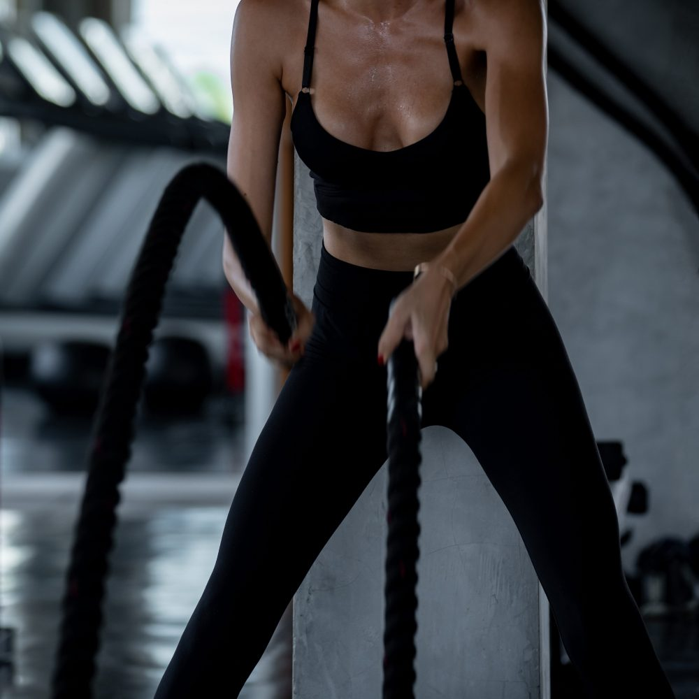 Young adult caucasian athlete sport bodybuilding woman in sportswear doing cardio battle rope exercise cross fit workout fitness during training class in gym sport club for strong healthy and slim