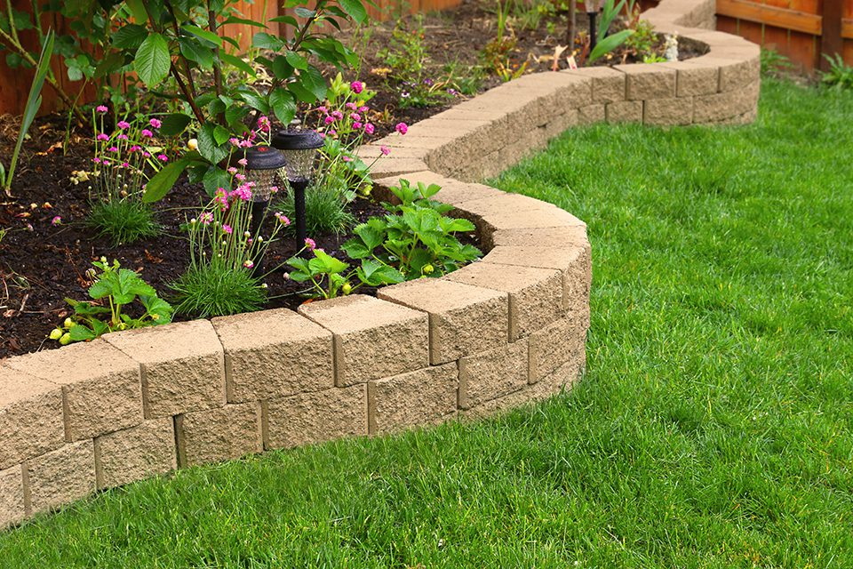 stone wall with perfect grass landscaping in garden with artific